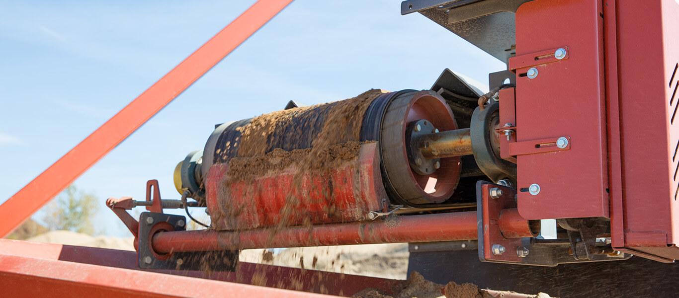 exterra belt cleaner from Superior Industries scraping a conveyor belt.